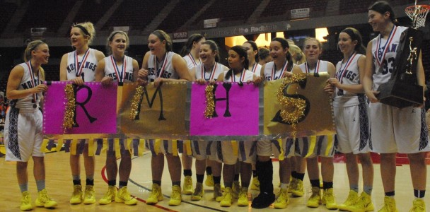 The girls basketball team pose with a sign made by fans and their second place trophy after the game.